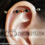 Fully healed 14g industrial piercing with a 3mm tangerine CZ with two genuine 3mm onyx gems.  Piercing by AJ.  Jewelry from Anatometal.
