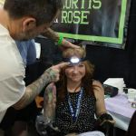 Bobby assisting Meghan with her head lamp while she tattoos.
